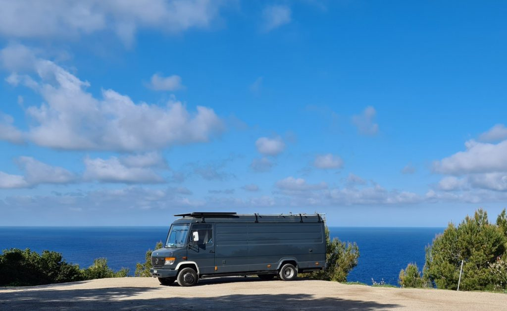Campervan parked in a scenic spot in front of the sea