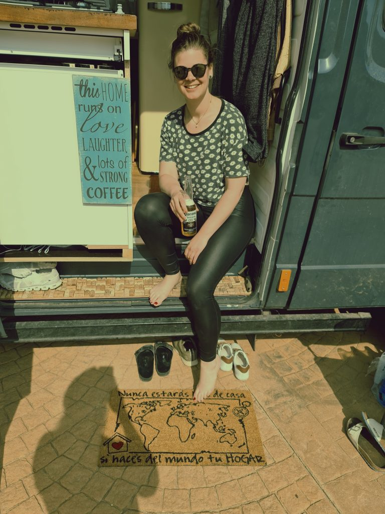 A woman sitting on the step of her campervan holding a bottle of beer. The sign next to her reads 'this home runs on love, laughter & lots of strong coffee'