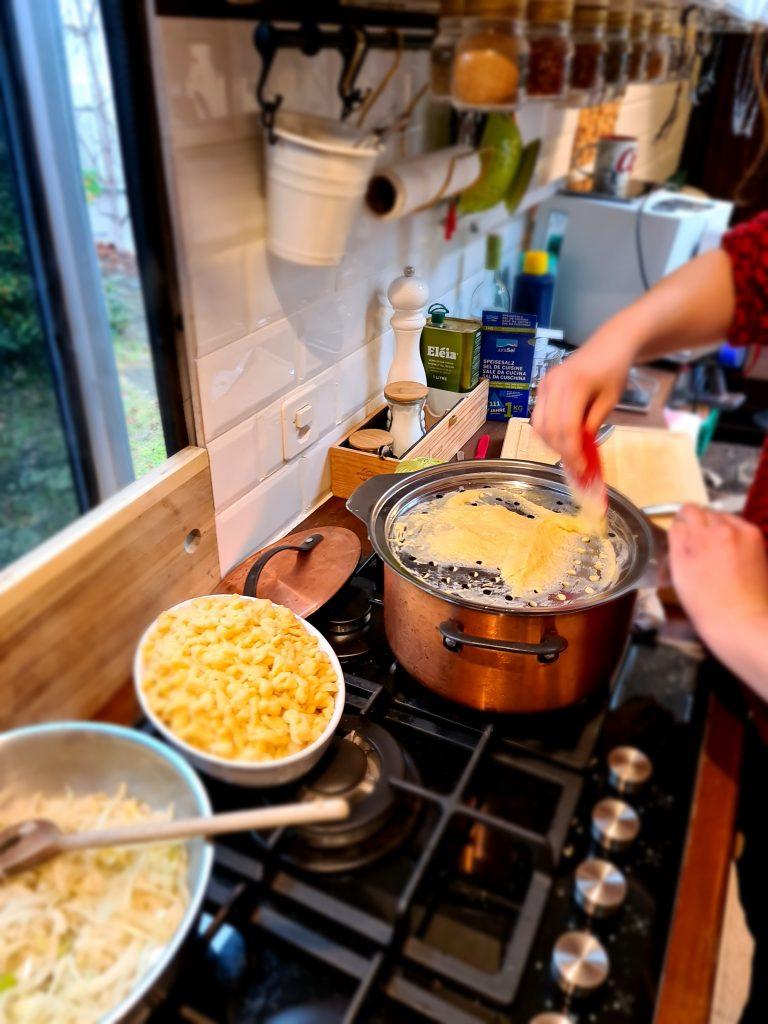 Close up of someone making Spätzli in a campervan kitchen