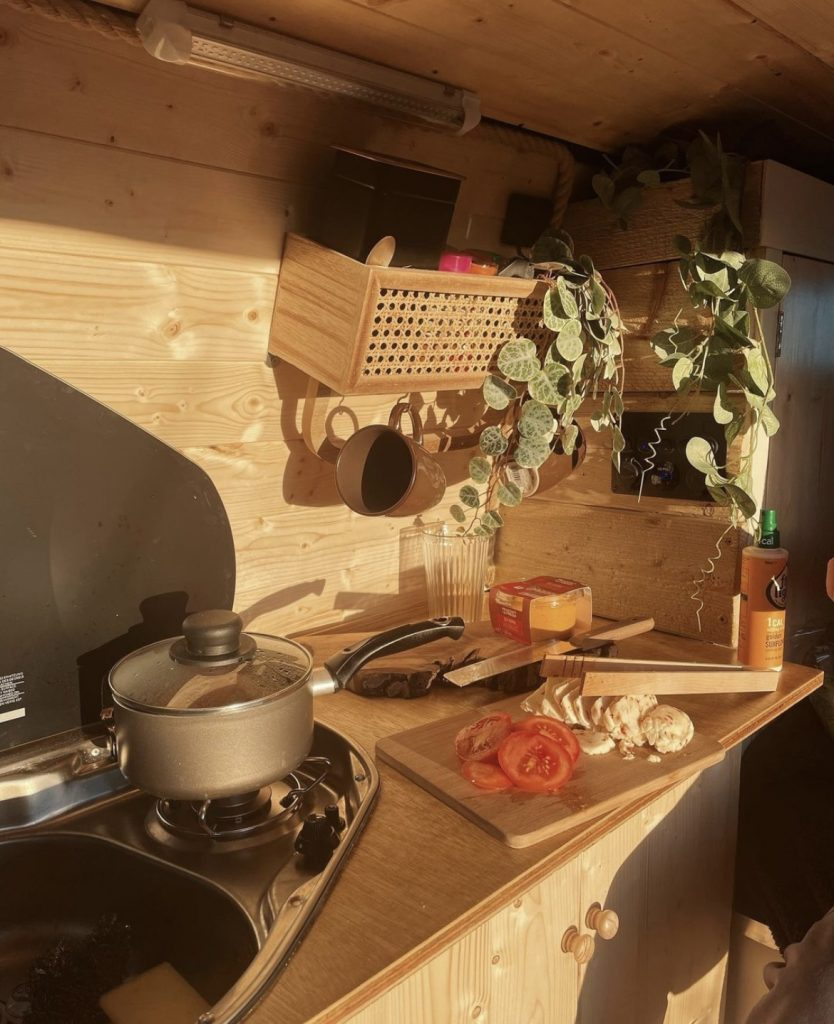 Inside the campervan kitchen. The walls, cupboard, and worktop are all made of light wood. There is a saucepan on a single hob and chopped fresh tomato and cheese on a chopping board.