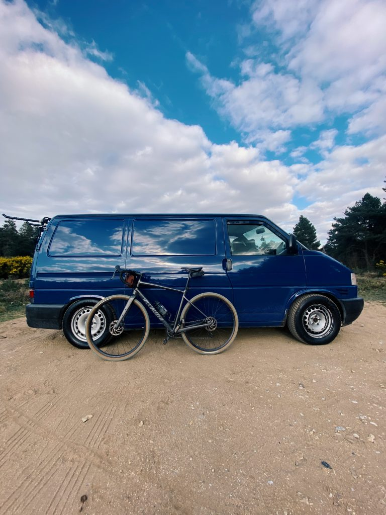 Blue T4 camoervan parked up on a dirt track. The view is side on on the drivers side and there is a bicycle leaning up against the side.