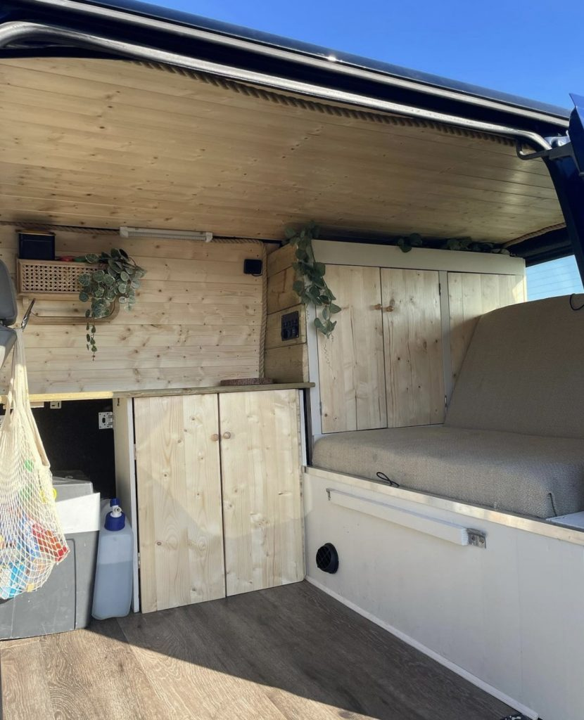 The inside of the campervan, there is light wood cladding throughout with a beige seat. There is a mesh shopping bag hanging up and green plants trailing down from the shelves.