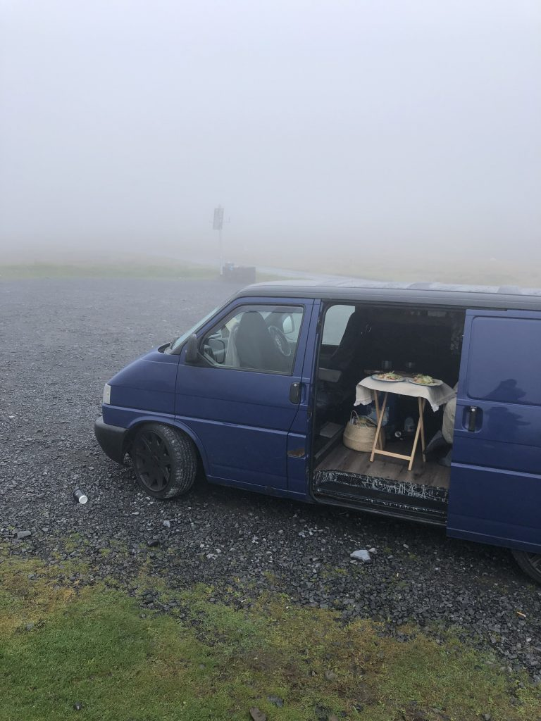A blue T4 campervan is parked up surrounded by fog. The sliding door is open & there is a table set for 2 with 2 plates of food.