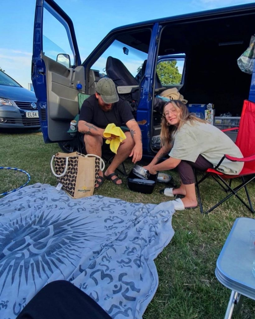 The couple are sat washing up their pans outside the van. Leanne is looking at the camera smiling, whilst washing a saucepan in a small black washing up bowl. Billy is sat on a camping chair with a tea towel in his hand, looking down.