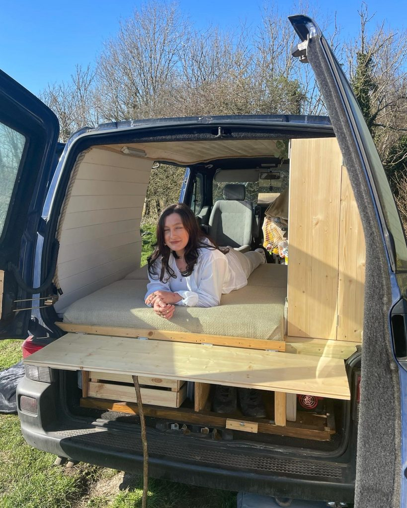 Leanne is dressed in white, she is lying on the bed on her front. The back doors of the campervan are open and the sun is shining, Leanne is smiling.