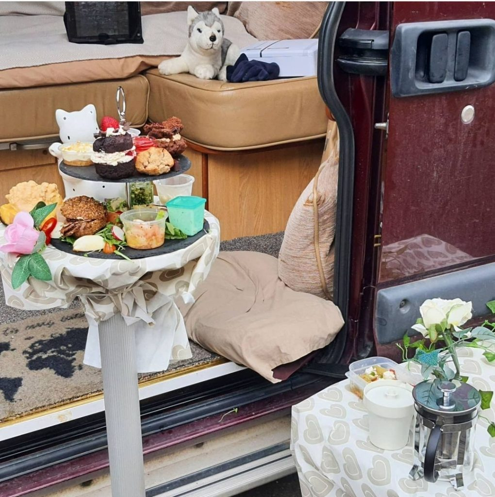 Afternoon tea presented on a table outside a campervan. There is a toy husky in the background