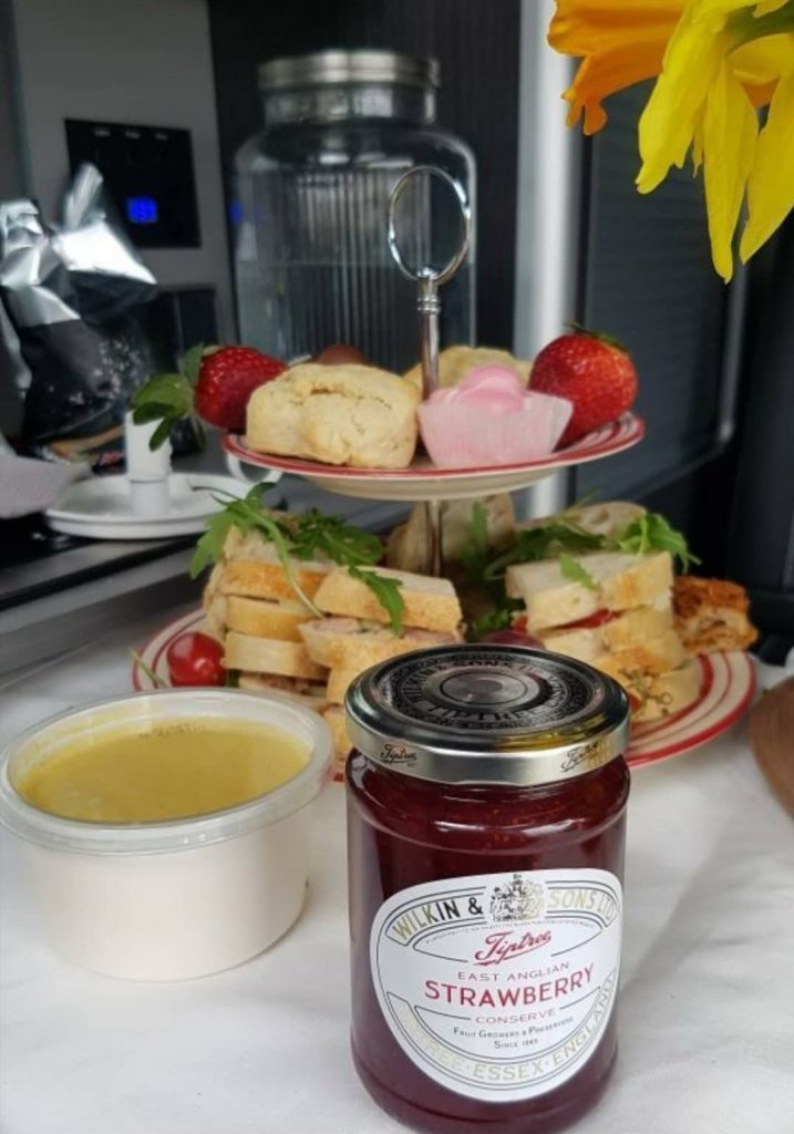 Afternoon tea presented on a red and white cake stand. On the top plate there are 2 scones and 2 french fancies as well as 2 straweberries. On the bottom plate are some sandwiches with salad