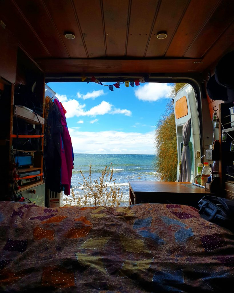 Looking out from the bed in the van, the back doors are open and the sea is in the background.