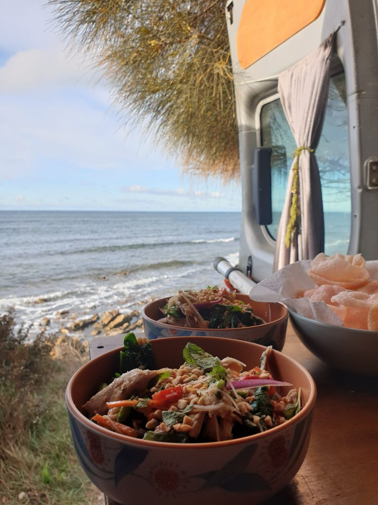 Two bowls of food on a table in the back of the van. The van doors are open and the sea can be seen.