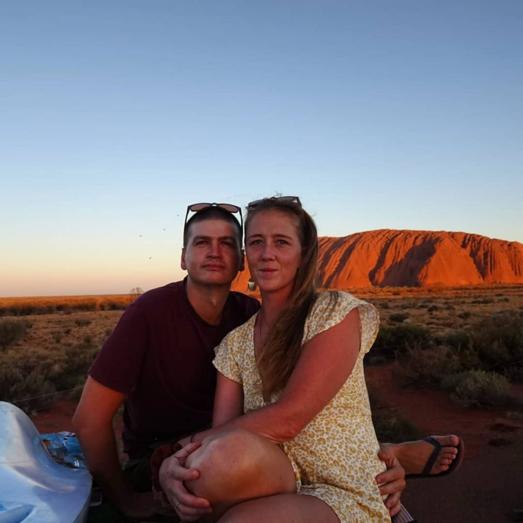 Sarahkai and Sam sitting together in the desert with the sun setting behind them.