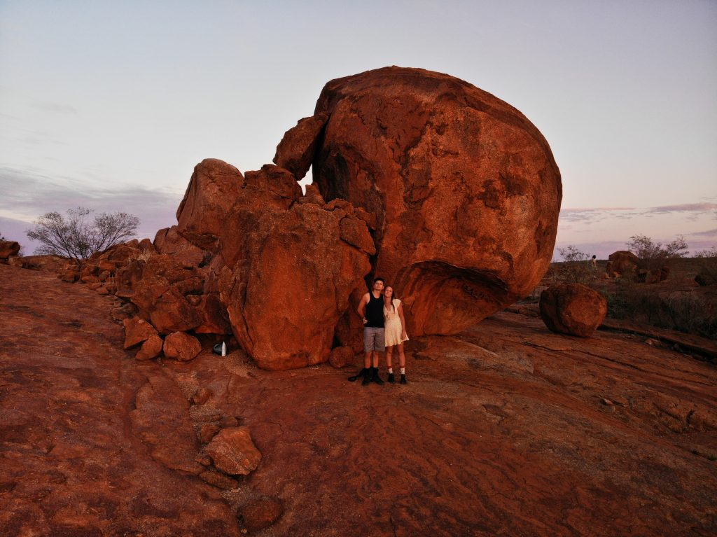 Sarahkai and Sam stood in front of a large red rock in the desert.