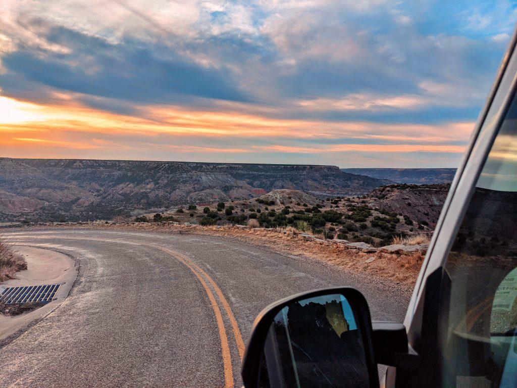 View from a van window, driving through a desert setting