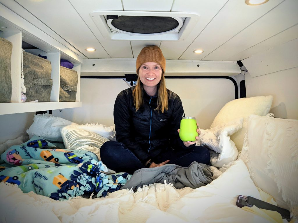 Girl sitting cross legged in her campervan. The walls are white and she is sat on the bed with a green cup in her hand