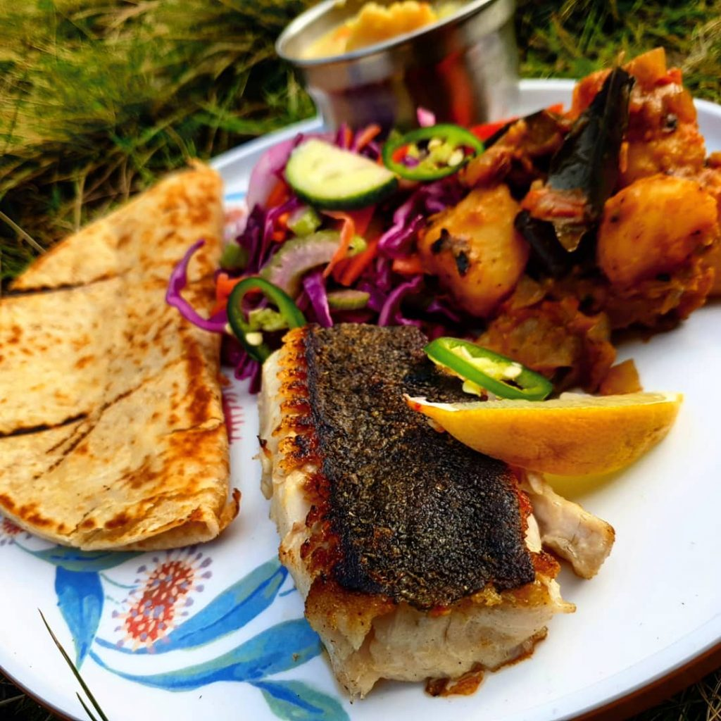 Plate of food in the sunshine. Charred fish, folded wrap and roasted vegetables.