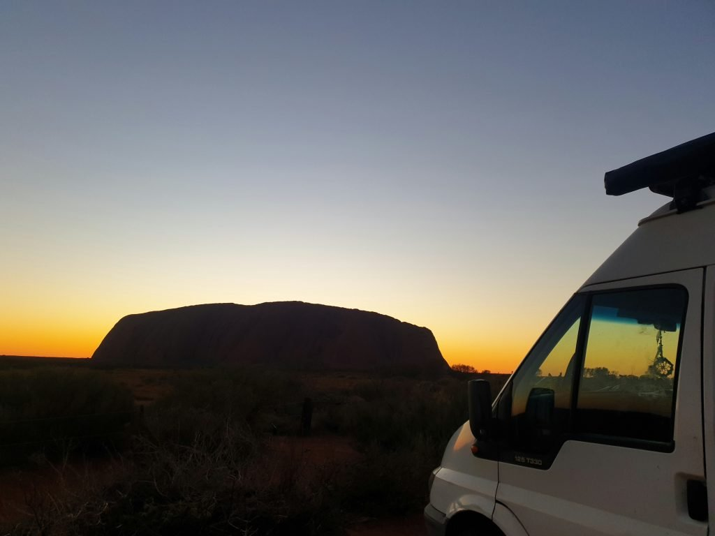Vinny the van in the foreground of the photo with a sunset behind a large rock in the background.