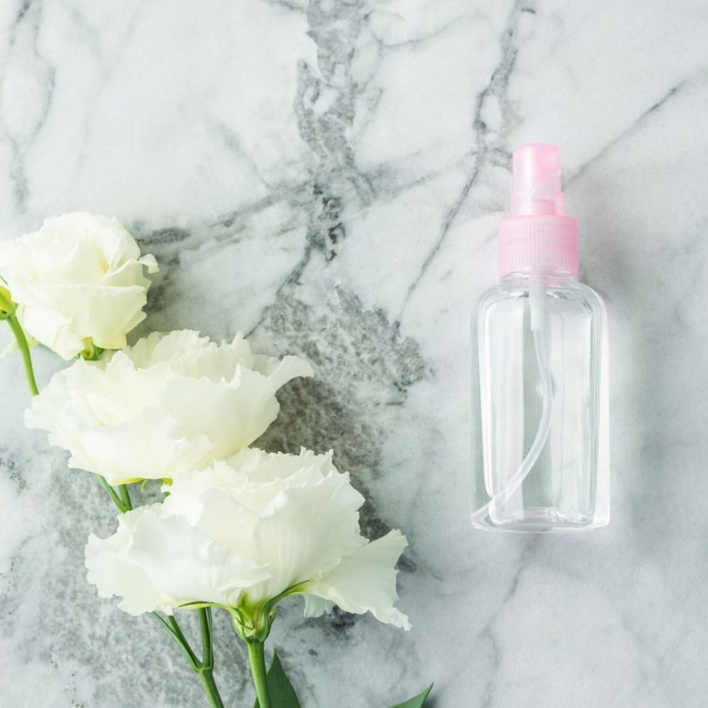 Re-useable plastic spray bottle with white flowers lying next to it