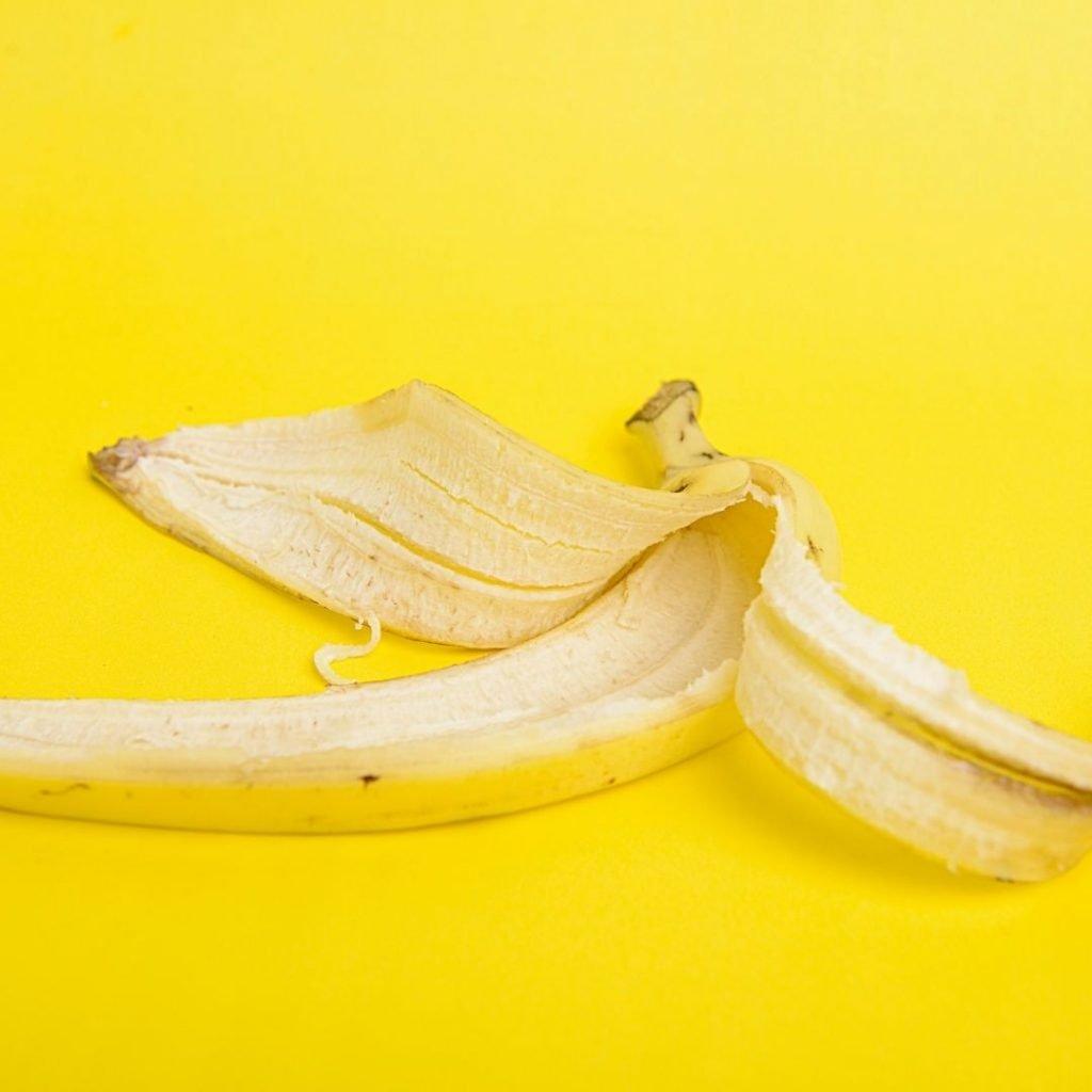 Banana peel on bright yellow background