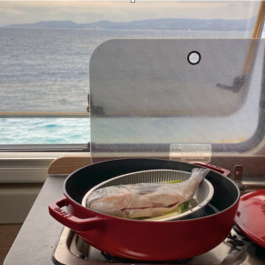 meal cooking on a stove in a campervan. There is a view of the sea through the window