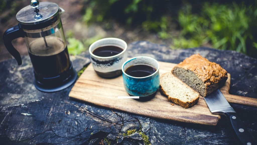 Coffee and sliced bread on a chopping board in the great outdoors