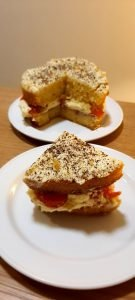 slice of victoria sponge with fresh cream and strawberries and grated chocolate on the top